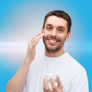 Mann trägt Creme im Gesicht auf