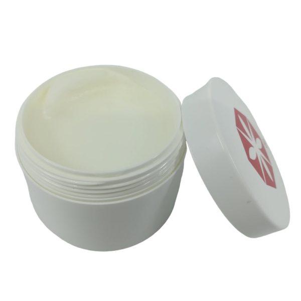 Heilsalbe Tiegel mit geöffnetem Deckel und weißer Creme